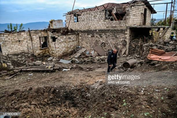 Ashot Aghajanian walks in the yard of his house, which is said was destroyed by last night Azeri shelling, in the city of Stepanakert on October 11...