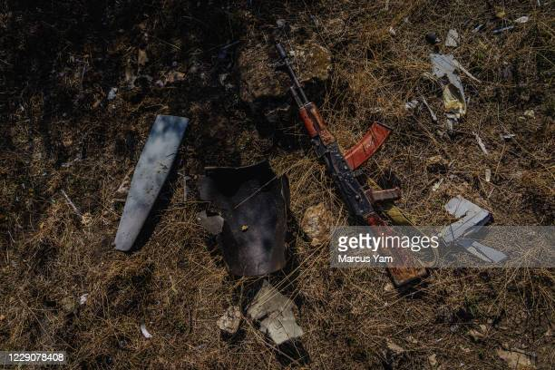 Ashot Sarkissian, 51 year-old artillery operator, lays his weapon on the ground as he examines the remaining debris of an Azerbaijan drone that...