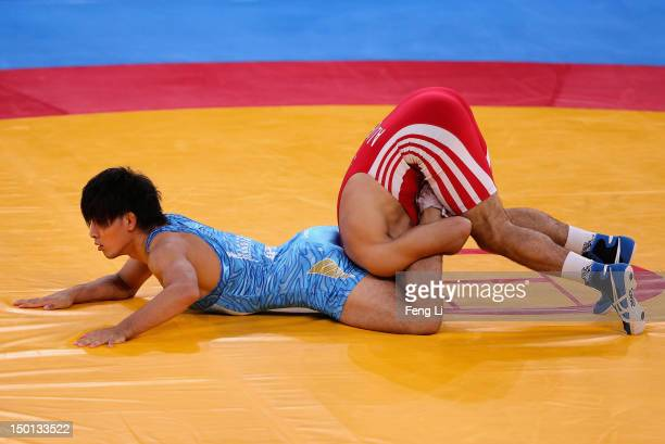 Ashraf Aliyev of Azerbaijan competes with Sohsuke Takatani of Japan during their Men's Freestyle 74 kg Wrestling qualification bout on Day 14 of the...