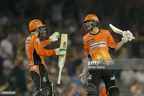 Ashton Agar celebrates with team mate Sam Whitman of the Perth Scorchers after hitting a 6 on the final ball to win the Big Bash League match between...