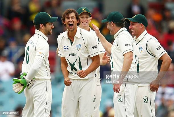 Ashton Agar of the Prime Minister's XI celebrates with team mates after taking the wicket of Ross Taylor of New Zealand during the tour match between...