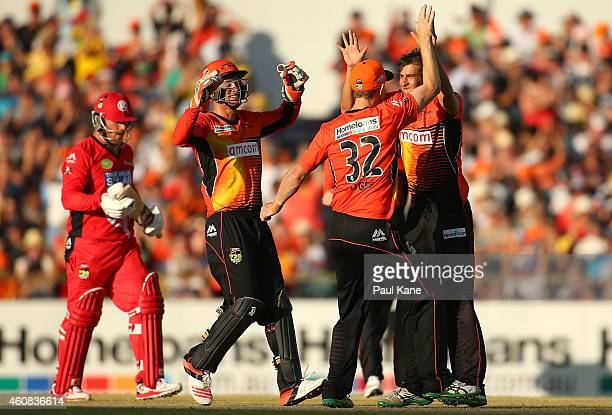 Ashton Agar of the Scorchers celebrates with team mates after dismissing Aaron Finch of the Renegades during the Big Bash League match between the...