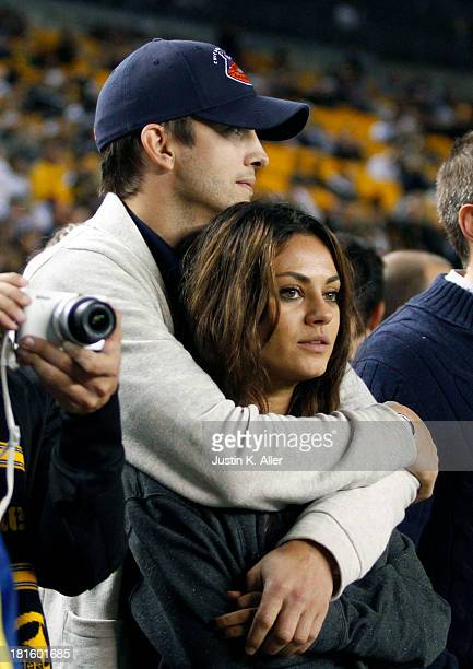 Ashton Kutcher and Mila Kunis look on from the sidelines before the game between the Chicago Bears and the Pittsburgh Steelers on September 22, 2013...