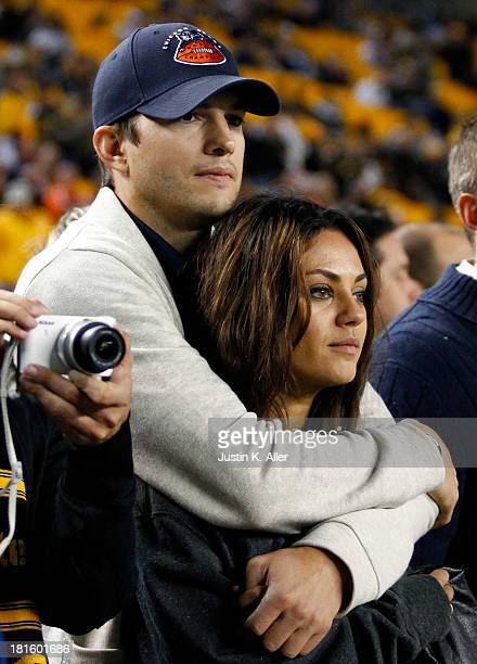 Ashton Kutcher and Mila Kunis look on from the sidelines before the game between the Chicago Bears and the Pittsburgh Steelers on September 22 2013...