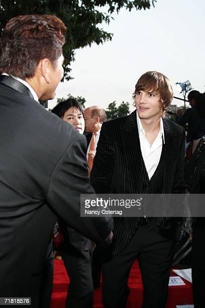 Ashton Kutcher greets exSeattle Mariners Pitcher Kazuhiro Sasaki on the red carpet at the World Premiere of 'The Guardian' September 7 2006 in...