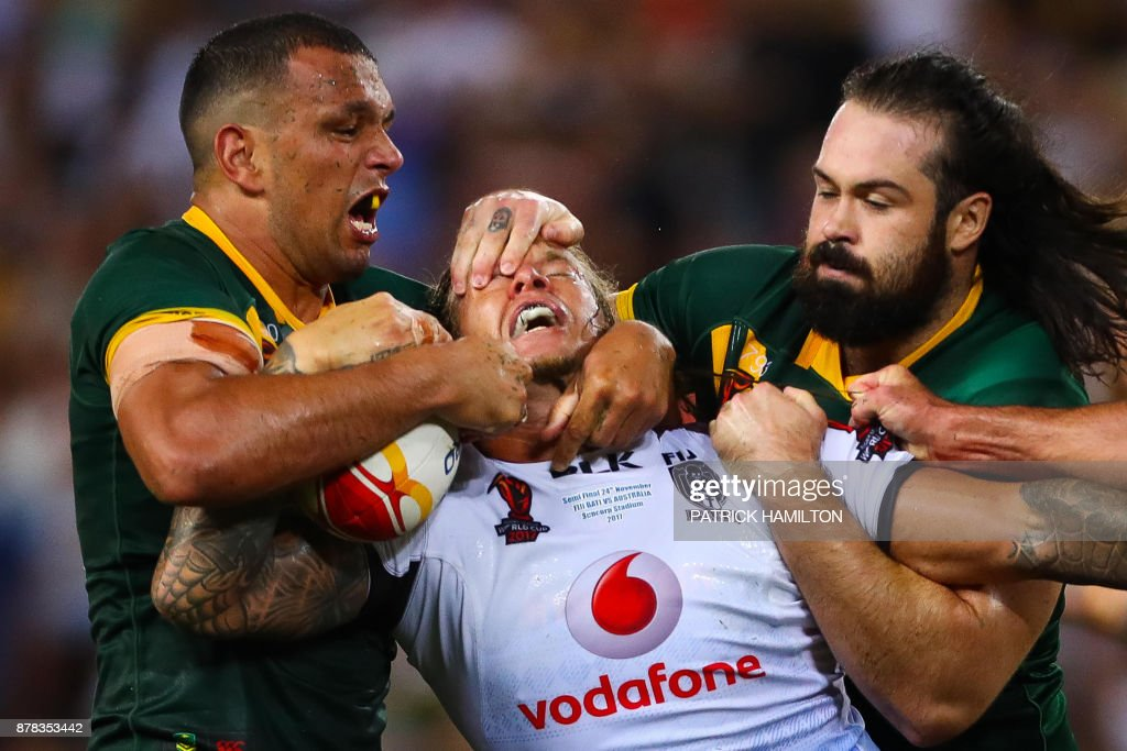 TOPSHOT - Ashton Sims of Fiji is tackled by Will Chambers (L) and Aaron Woods (R) of Australia during the Rugby League World Cup men's semi-final match between Australia and Fiji at the Suncorp Stadium in Brisbane on November 24, 2017. / AFP PHOTO / Patrick HAMILTON / --IMAGE
