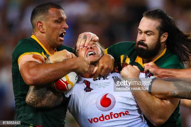 TOPSHOT Ashton Sims of Fiji is tackled by Will Chambers and Aaron Woods of Australia during the Rugby League World Cup men's semifinal match between...