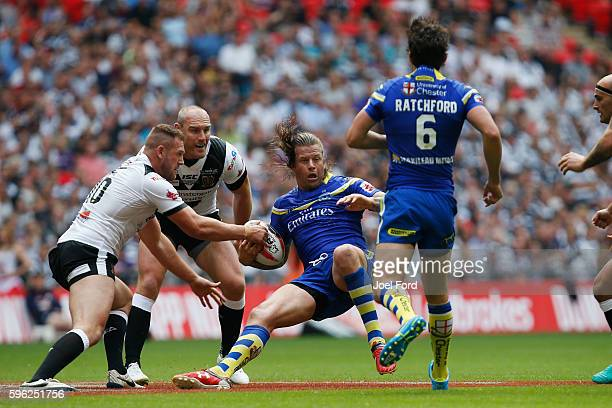 Ashton Sims of the Warrington Wolves is tackled during the Ladbrokes Challenge Cup Final between Hull FC and Warrington Wolves at Wembley Stadium on...