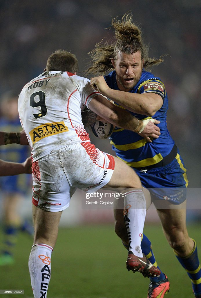 Ashton Sims of Warrington Wolves is tackled by James Roby of St Helens during the First Utility Super League match between St Helens and Warrington Wolves at Langtree Park on March 19, 2015 in St Helens, England.