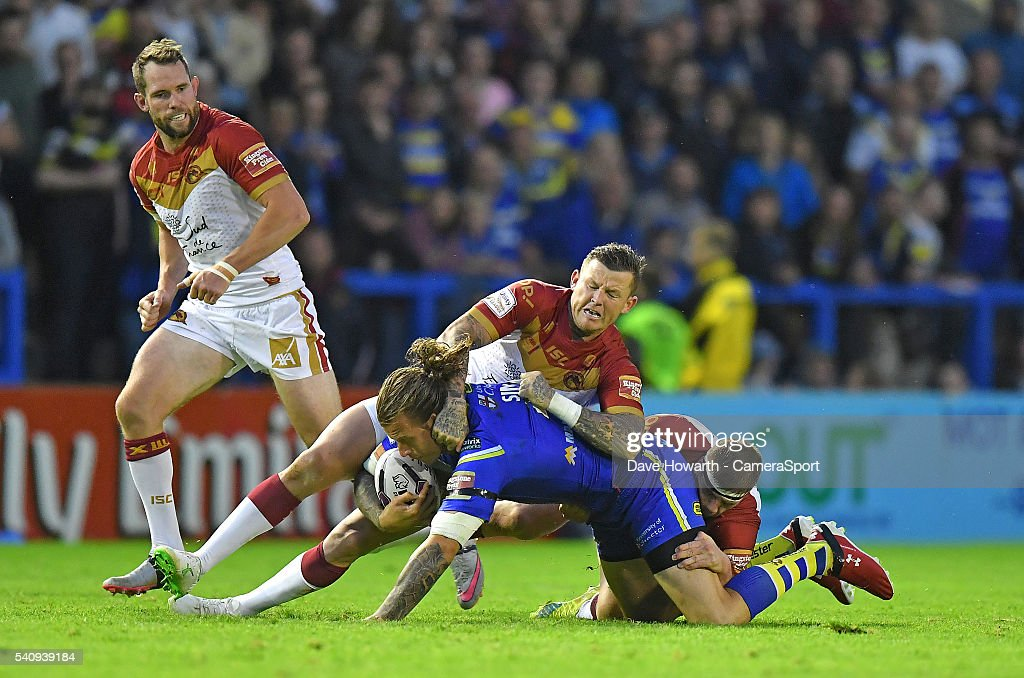 Ashton Sims of Warrington Wolves is tackled during the First Utility Super League Round 19 match between Warrington Wolves and Catalans Dragons at the Halliwell Jones Stadium on June 17, 2016 in Warrington, United Kingdom.