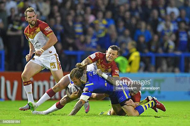 Ashton Sims of Warrington Wolves is tackled during the First Utility Super League Round 19 match between Warrington Wolves and Catalans Dragons at...