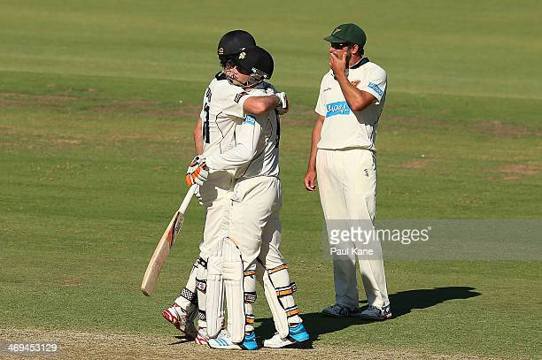 Ashton Turner and Sam Whiteman of the Warriors celebrate defeating the Tigers as Ben Hilfenhaus of the Tigers looks on during day four of the...