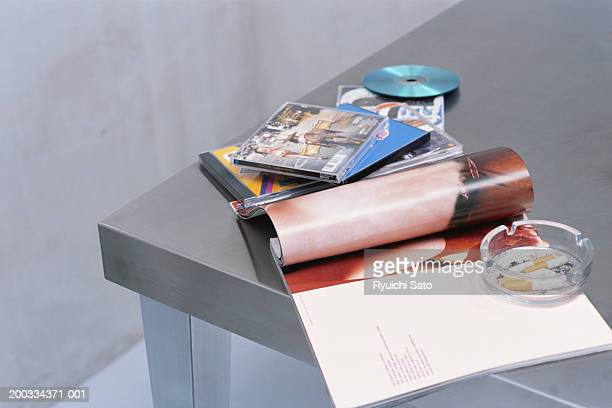 Ashtray, CD's and magazines on table, elevated view