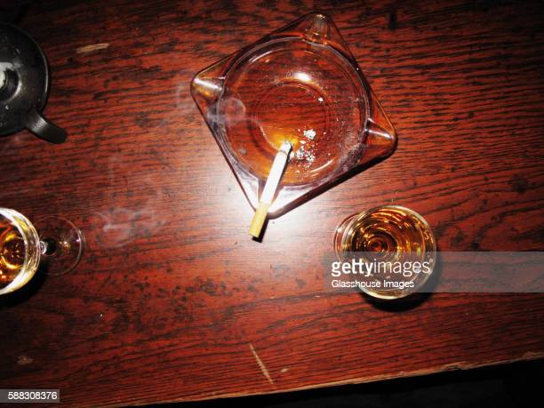 Ashtray With Cigarette and Wine Glasses on Table, High Angle View