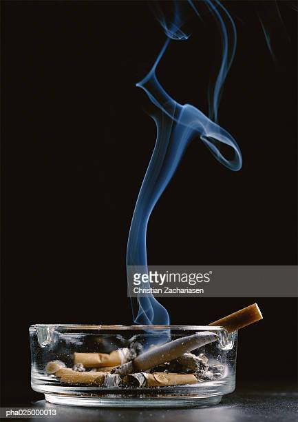 Ashtray with cigarette butts and lit cigarette emitting smoke against black background