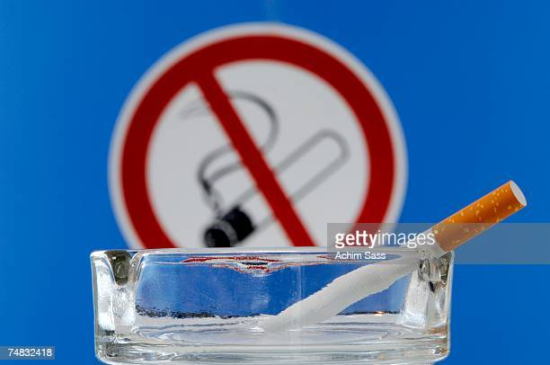 Ashtray with cigarette, non-smoking sign in background, close-up