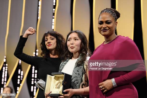Asia Argento raises her arm as actress Samal Yeslyamova receives the receives the Best Actress award for 'Ayka' as Jury member Ava DuVernay presents...