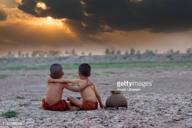 asia boy with friend sitting on dry ground. - emergencies and disasters stock pictures, royalty-free photos & images