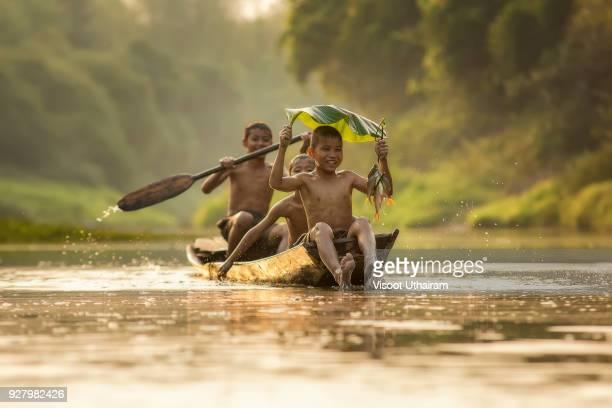 Asia children enjoying in boat on beautiful river.