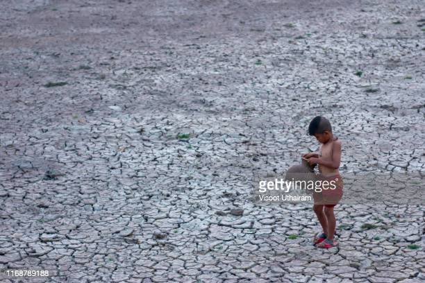 asia children standing on cracked earth in the arid area. - scarce stock pictures, royalty-free photos & images