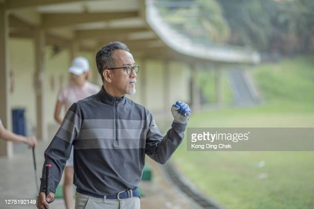 asia chinese senior man golfer happy get a success shot at driving range during rainy day. - individual event stock pictures, royalty-free photos & images
