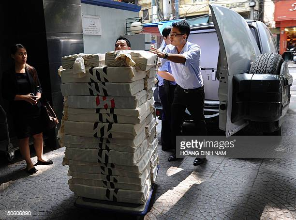 Asia Commercial Bank employees unload a pile of bags containing bricks of dong bank notes sent in from the state bank in Hanoi on August 23, 2012....
