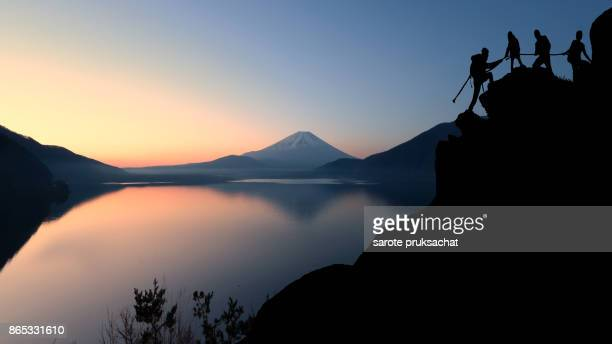 asia couple hiking help each other silhouette in mountains with sunlight and background view of mt. fuji , japan. team teamwork join hands partnership concept . - soporte conceptos fotografías e imágenes de stock