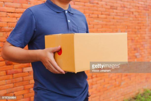 Asia delivery man are holding a cardboard box delivery