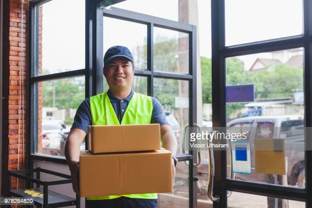 Asia delivery man are holding a cardboard box delivery to his customer.