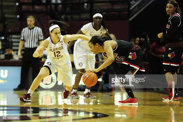 Asia Durr guard Louisville Cardinals stumbles with the basketball against Brittany Brown guard Florida State University Seminoles in an Atlantic...