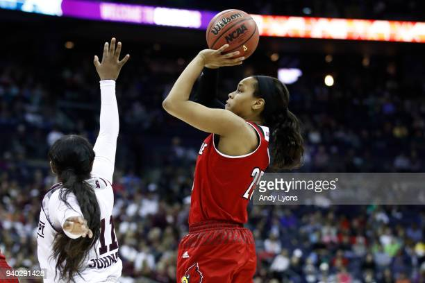 Asia Durr of the Louisville Cardinals attempts a shot defended by Roshunda Johnson of the Mississippi State Lady Bulldogs during the second half in...