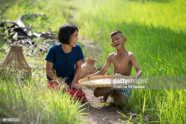 asia farmer child happiness and siting in farmland. - myanmar stock pictures, royalty-free photos & images