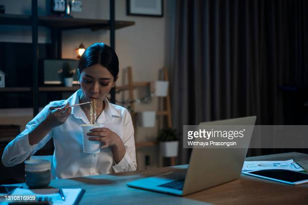 asia freelance smart business women eating instant noodles while working on laptop - urgency stock pictures, royalty-free photos & images