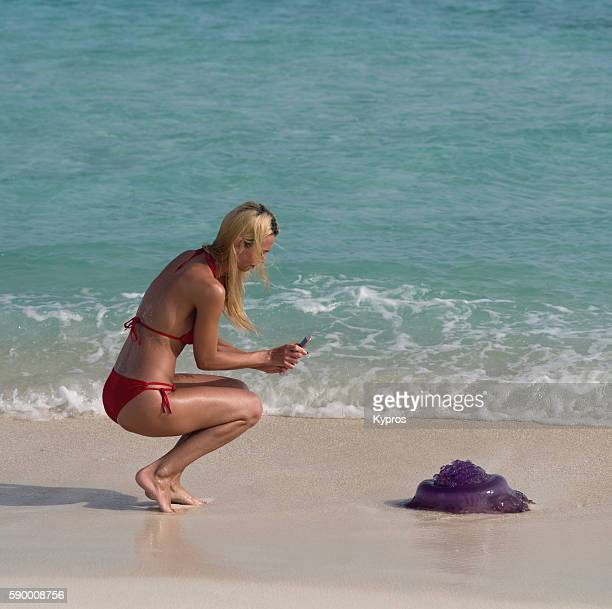 Asia, Maldives, Close Up Of Young Caucasian Woman Using  Smartphone Camera To Photograph Large Jellyfish  On Beach