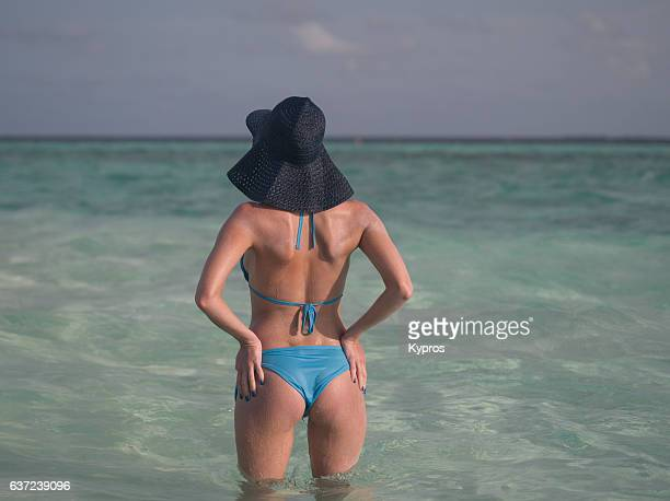 asia, maldives, rear view of young woman standing on beach wearing blue bikini and sun hat - beautiful female bottoms stock pictures, royalty-free photos & images