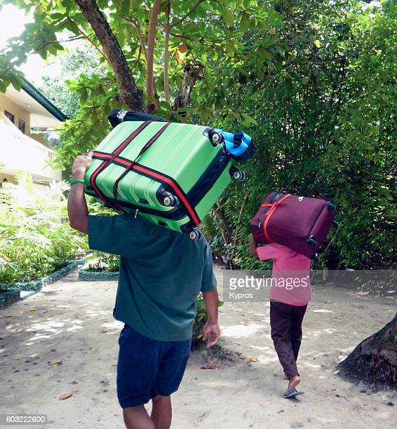 Asia, Maldives, View Of Porters Carrying Luggage On A Tropical ISland