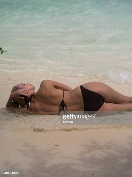 asia, maldives, view of young woman wearing bikini on beach - fesses femme gros plan photos et images de collection