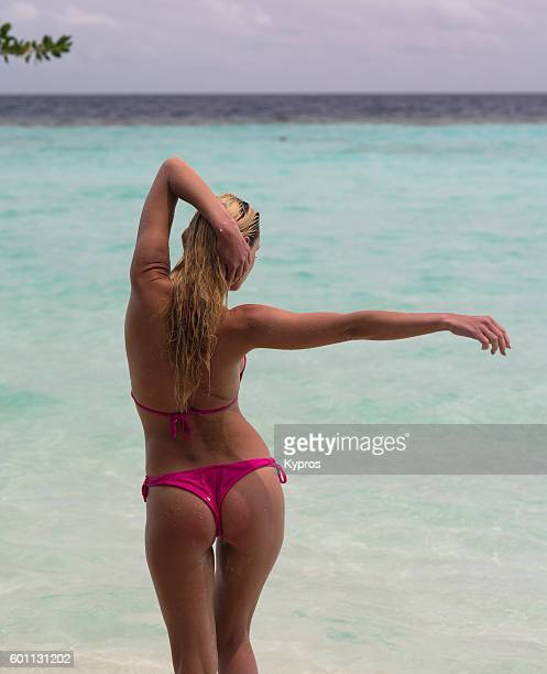 asia, maldives, view of young woman wearing bikini on beach with arms raised - fanny pic fotografías e imágenes de stock