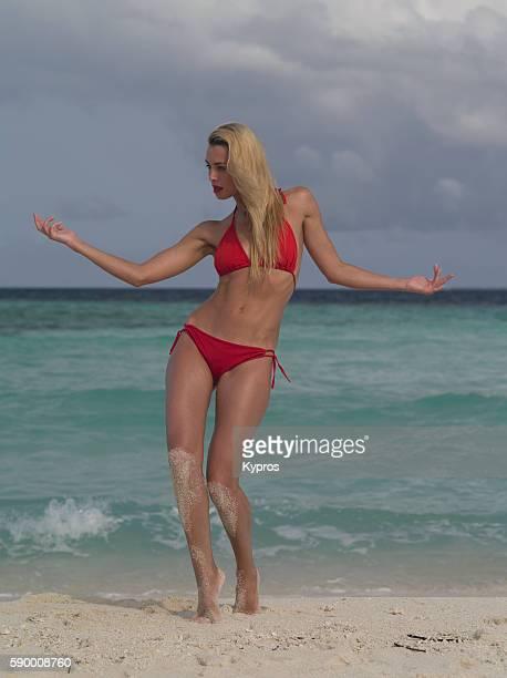 Asia, Maldives, Young Woman Wearing A Bikini Walking On A Tropical Beach
