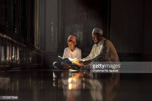 asia muslim reading quran in mosque. islamic concept. - koran stock pictures, royalty-free photos & images