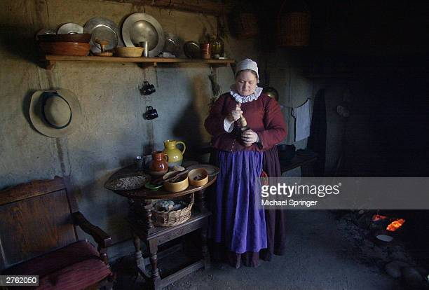 Asia Poppers who portrays colonist Tryphosa Tracy prepares fritters in her oneroom house November 25 2003 at Plimoth Plantation in Plymouth...