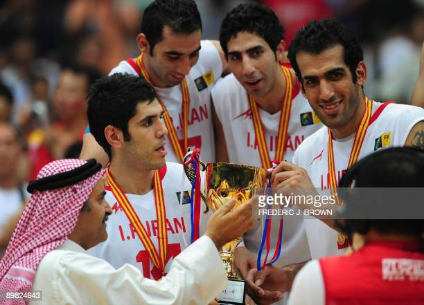 Asia President Sheikh Saud Ali Al Thani presents the championship trophy to Iran's Mohammadsamad Bahrami and Hamed Hadadi following victory over host...