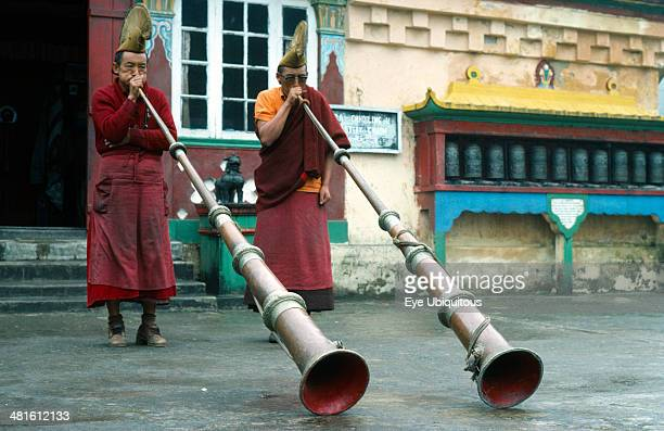 Asia Two Yellow Sect Buddhist monks at Choling monastery near Darjeeling playing long horns
