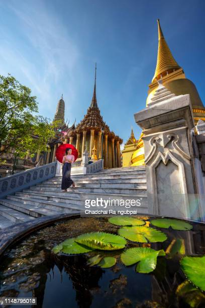 asia women tourists are travel taking a giant statue in phra kaew temple.wat phra kaew of thailand, the emerald buddha temple and the grand palace. travel thailand tourist concept. - wat stock pictures, royalty-free photos & images