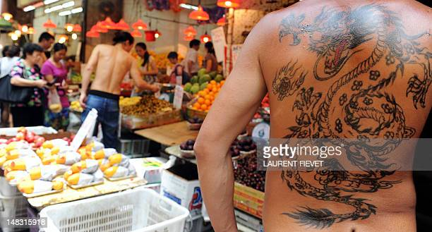 AsiaChinaeconomyANALYSIS by Stephen Coates A fruit and vegetable vendor sports a dragon tattoo at an open market in Hong Kong on July 14 2012 Bad...