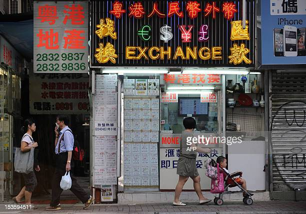 STORY 'AsiaChinaeconomygrowth ANALYSIS' by Stephen Coates In this picture taken on October 7 pedestrians walk past a money exchange outlet in Hong...