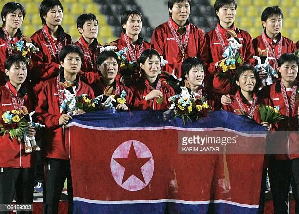 Asiad2006FblwomenPRKJPN North Korean goalkeeper Jon Myong Hui poses with teammates after their victory over Japan in the women's gold medal football...