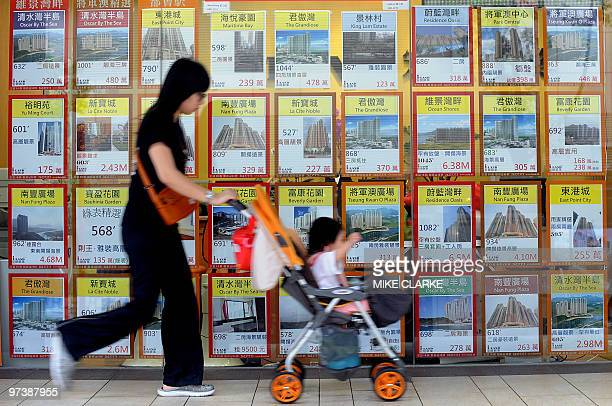 AsiaeconomypropertyFOCUS by Martin Abbugao A woman pushes her child past a property agent window in Hong Kong on March 3 2010 Asian countries fearing...