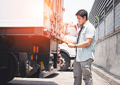 asian truck driver holding clipboard is