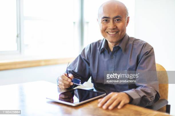 Asian Adult Male sitting in office at desk with bright windows providing back light